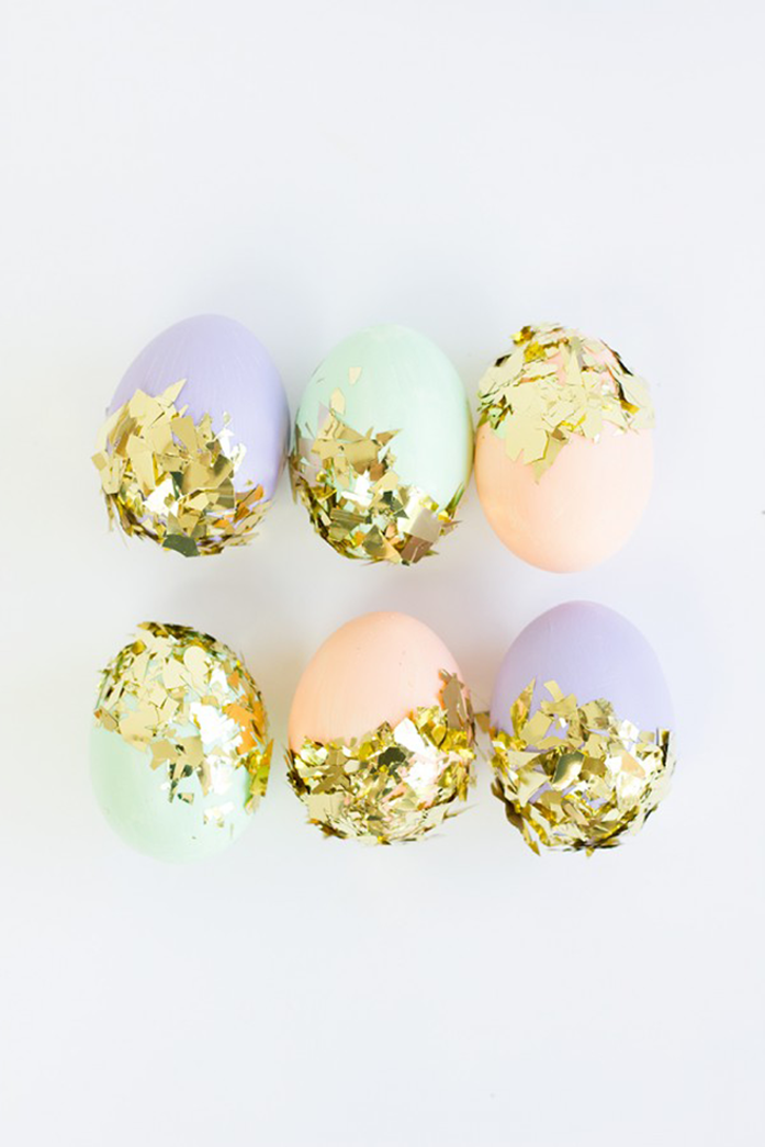 gold leaf used to partially decorate six eggs, dyed in pale pink, pale teal and pale violet, easter egg decorating, white background