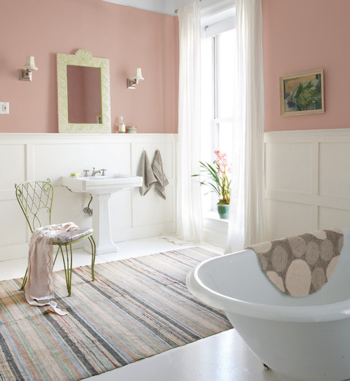 striped multicolored faded rug, in bathroom with pink pastel walls, and white paneling, shabby chic decorating, antique chair and white bathtub, and large window, with sheer cream curtains