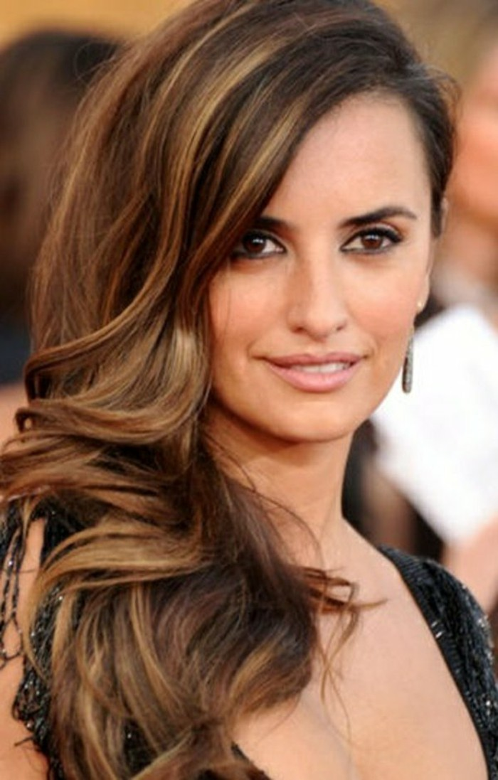 highlighted dark brunette hair, with a deep side parting, and partially curled, worn by penelope cruz, with natural-looking make up, and sparkly black top