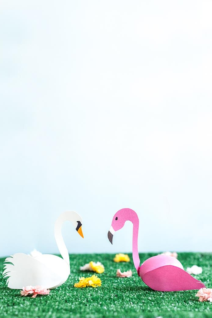 coloring easter eggs, swan and flamingo, made from eggs, one white one dyed pink, with paper wings and heads, placed on artificial green grass, with several tiny fake flowers
