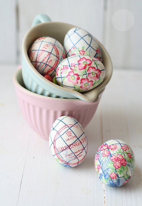 pastel pink and blue jugs, containing three white eggs, decorated with paper napkin decoupage, coloring easter eggs, two more eggs are placed outside of the jug