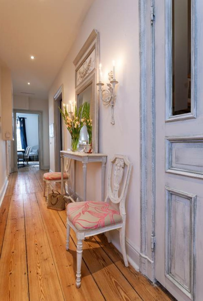 shabby chic pale blue door, solid wooden floorboards, small white antique table with two matching chairs, near a large mirror, and wall candleholder with lit candles, hallway design ideas