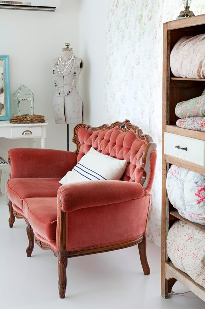 french sofa in vivid red, with buttons and brown legs and ornaments, cream cushion with three navy stripes, brown and cream wardrobe with duvets
