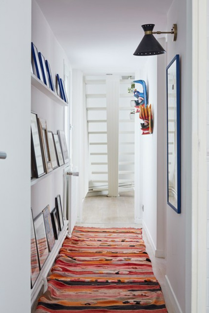 brightly lit corridor, white walls and a multicolored rug, hallway decorating ideas, several shelves with farmed images on one wall, a large singe image in blue frame on opposite wall