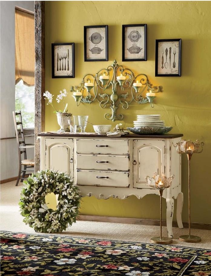 plates and glasses, on large cupboard in cream, with chipped paint effect, near a floral rug in black and green, red and blue, a wreath and several candle holders