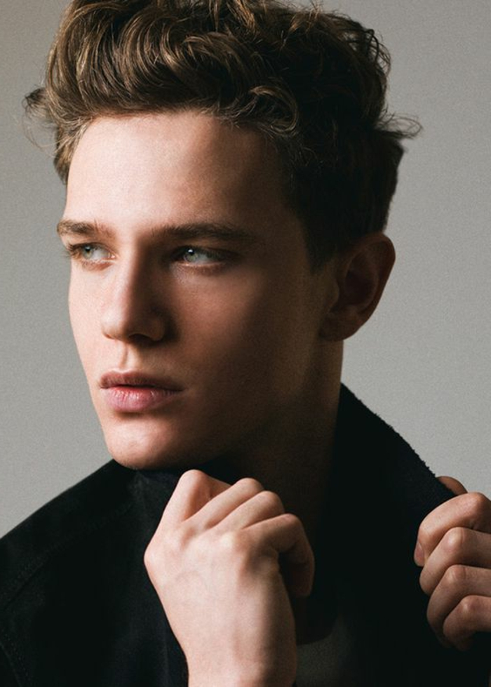 serious-looking young man, in black coat, with brown hair, worn in rockabilly-style