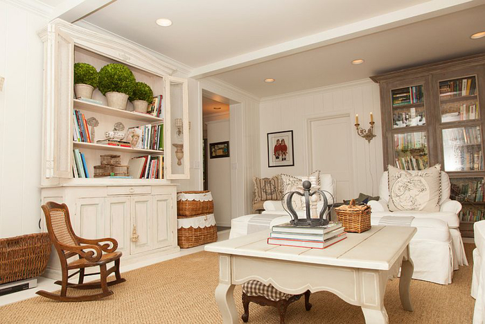 wooden table in vintage style, painted white and decorated with books and other objects, shabby sheek, rocking chair and vintage wardrobes, in white and brown