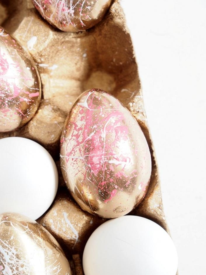 gold painted egg, decorated with drizzles of pink and white paint, easter egg decorating, placed inside a cardboard egg box, near other similar and plain eggs