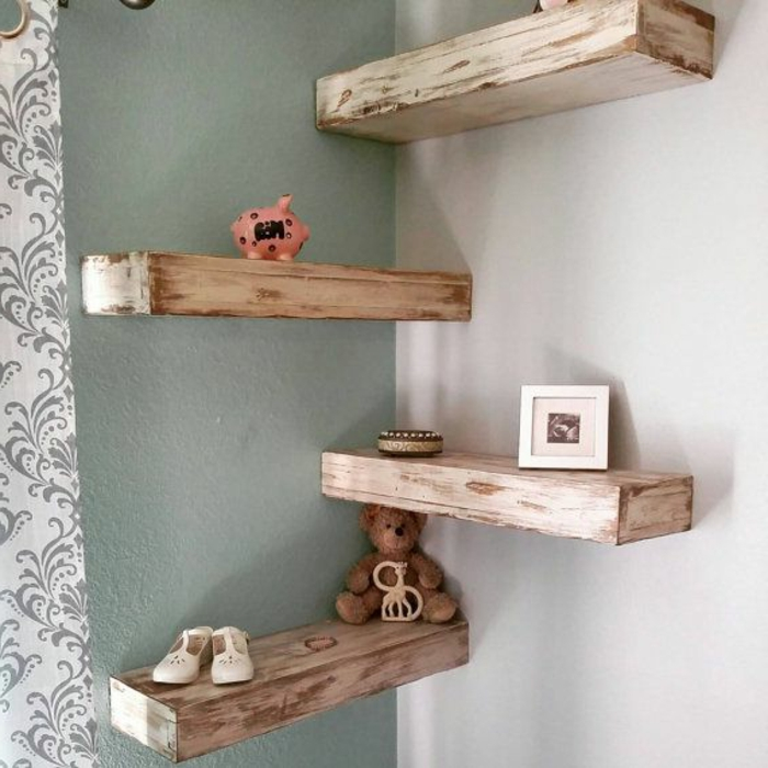four massive wooden planks, unevenly painted in cream, mounted as shelves on grey and white walls, teddy bear and baby shoes, photo in frame and piggy bank