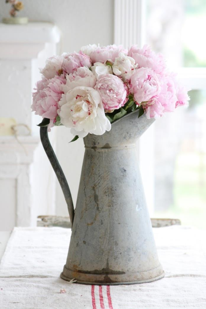 jug made from rusty metal, with curved handle, containing pale pink peonies, country cottage furniture, rough cream tablecloth, with three red stripes