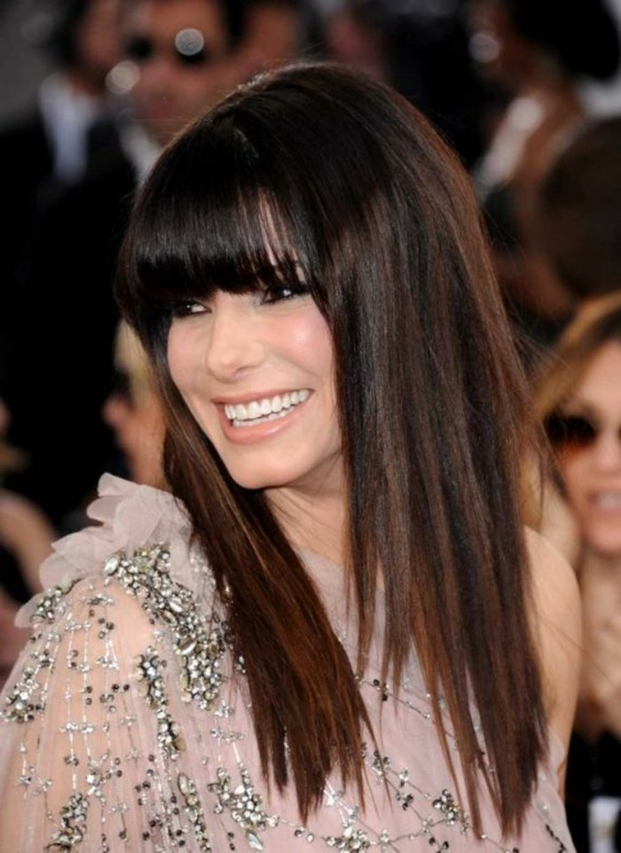 smooth straight dark hair, with long bangs and, and reddish-brown highlights, on sandra bullock, dark haired actresses, wearing pale pink, semi-sheer dress, with silver beads