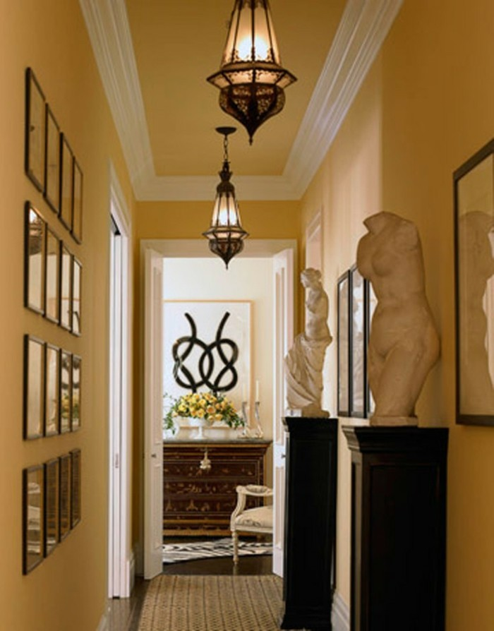 sixteen framed images, mounted on peach colored wall, hallway furniture ideas, two black columns, with a statue each, two ornate ceiling lamps