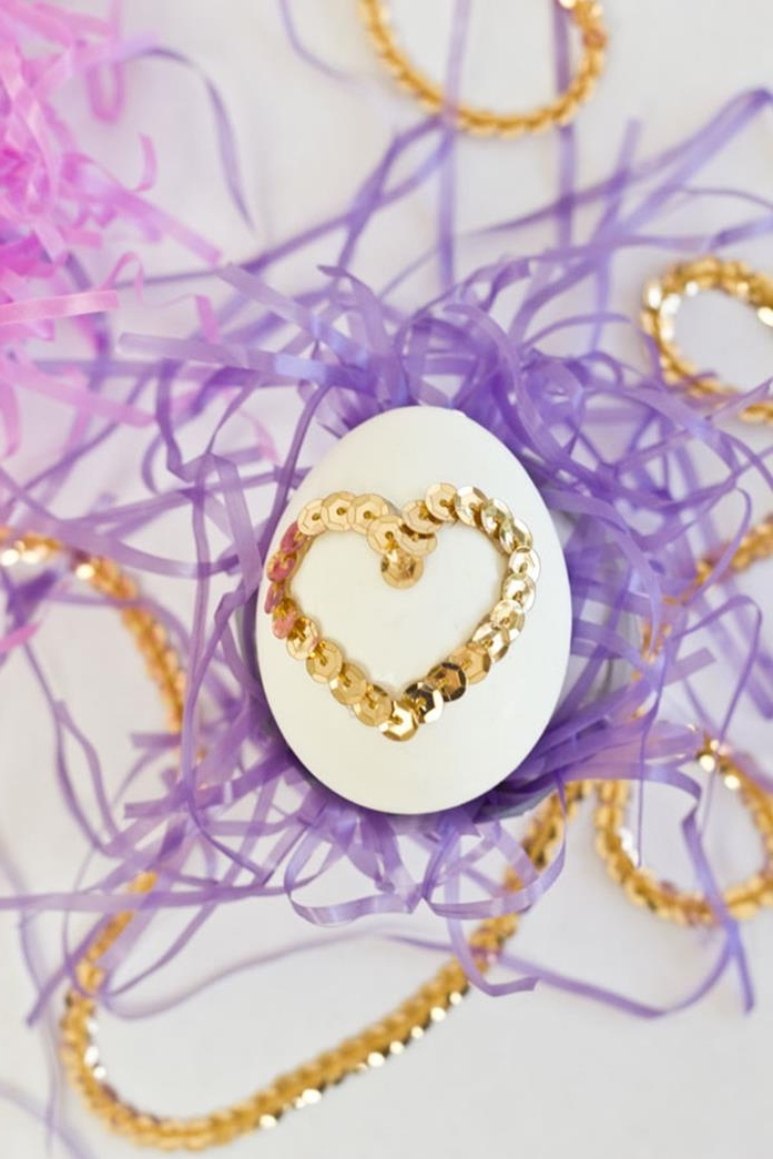 plain white egg, decorated with heart shape, made from golden sequin rope, placed on purple and pink easter grass