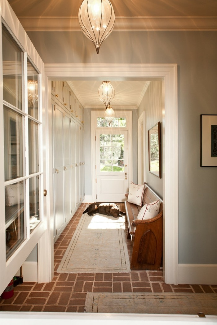 sleeping dog lying on beige rug, near a front door, inside hall with pale blue walls, and brown tiled floors, long hallway runners, various cupboards and a wooden settee