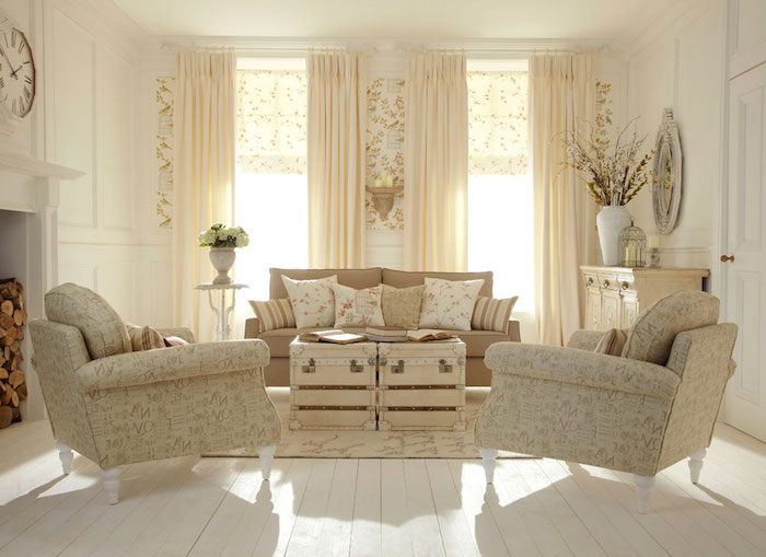 bright room with two windows, cream curtains and wooden floor, pale beige shabby chic sofa, with several cushions, patterned cream colored armchairs, coffee table made of suitcases