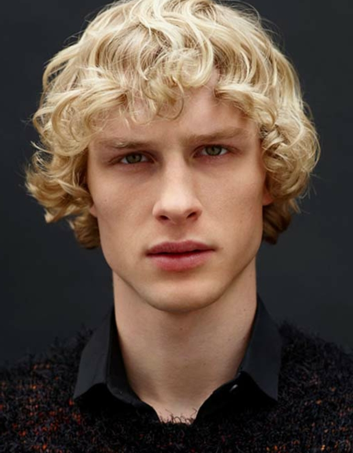 curly shaggy light blonde hair, long hairstyles for boys, worn by blue-eyed man, in black shirt, and black and red jumper