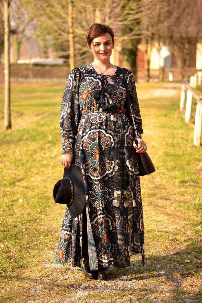 short-haired smiling woman, with pixie cut, wearing black maxi dress, with long sleeves, and colorful floral pattern, holding large bohemian style hat