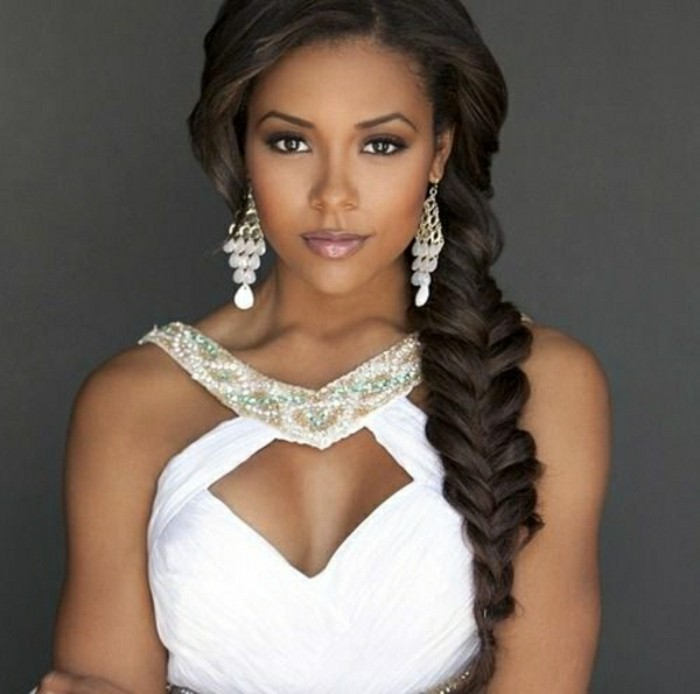 afro hair woven in a thick side braid, on woman in white evening dress, decorated with beads, wearing large white earrings, and subtle make up