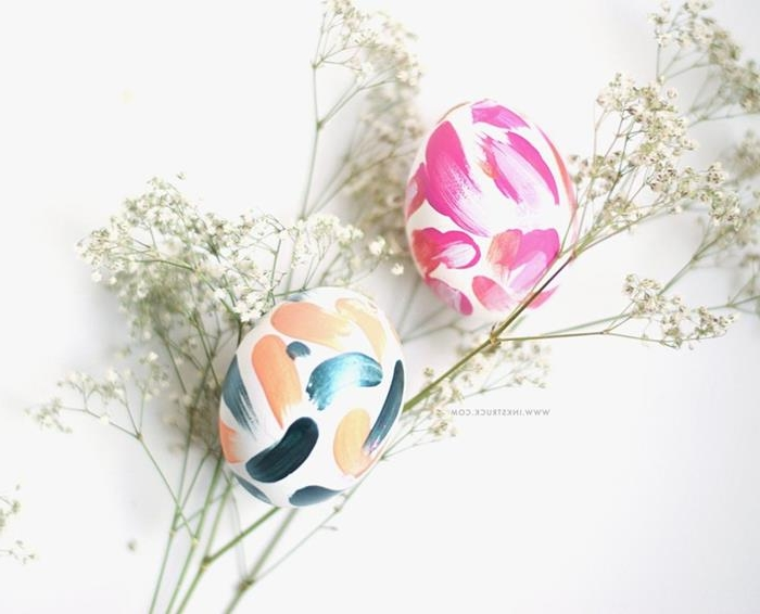 delicate white flowers, near two white eggs, decorated with paint daubs, in hot pink, peach and navy, how to dye easter eggs