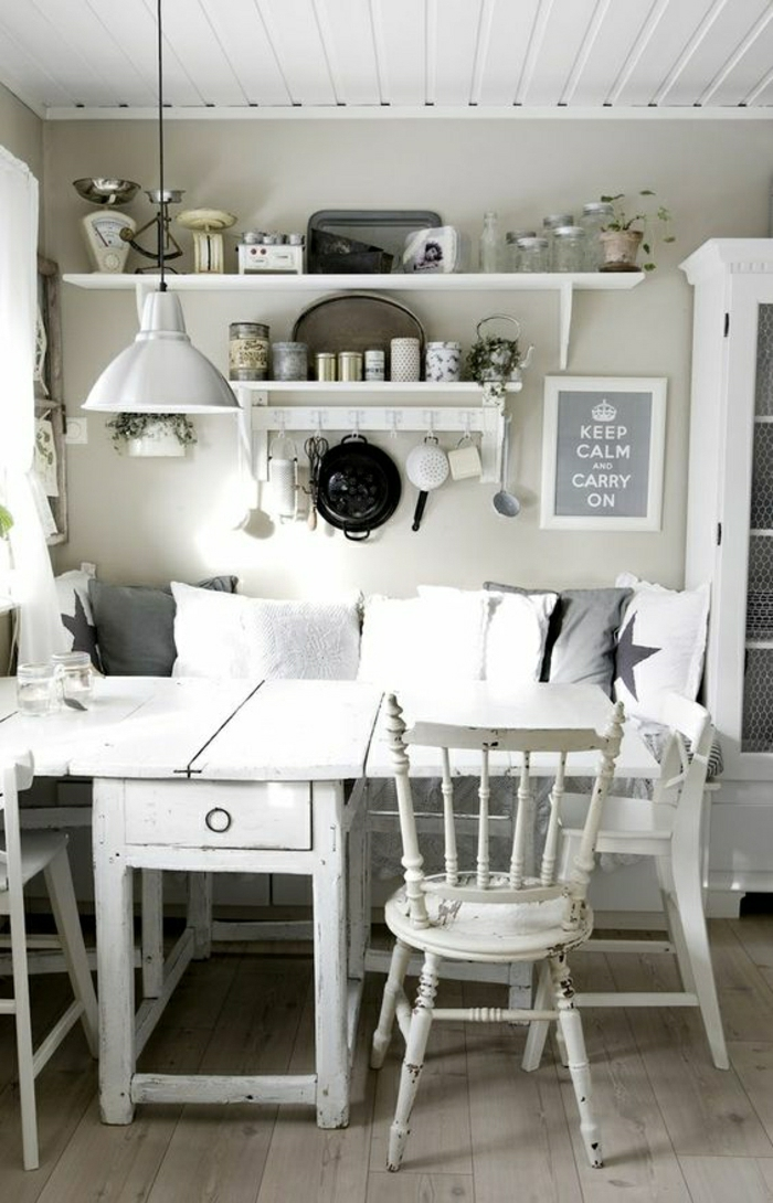 several cushions in dark grey and white, on shabby chic sofa, near a white, antique kitchen table, with matching chairs