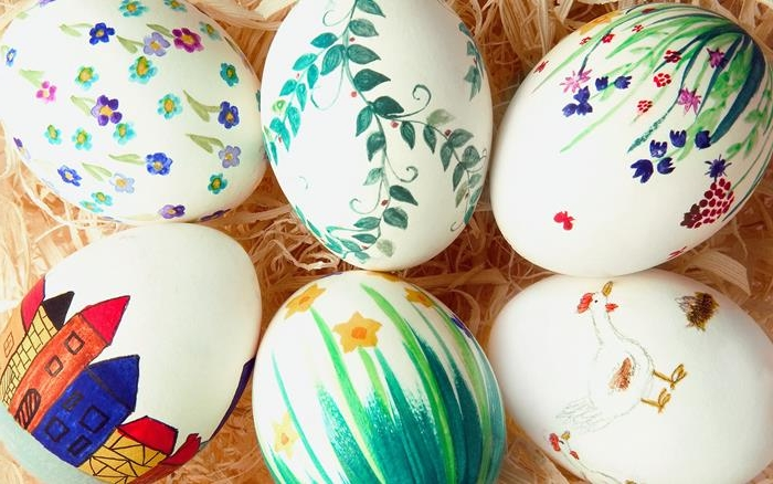 easter eggs in white, decorated with simple drawings, of different flowers, houses and birds, all done in markers