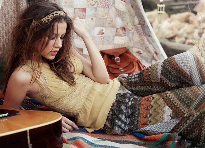 yellow top with lace, and wide patterned culottes in earthy colors, worn by young brunette woman, with woven hair ornament, lying on a striped blanket