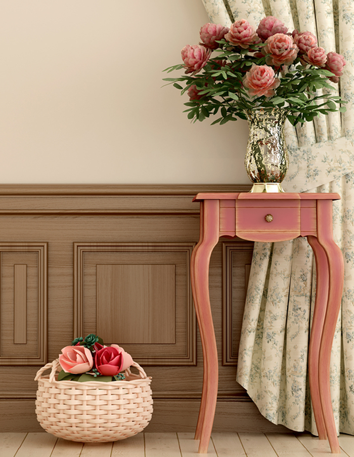 digital 3D illustration, depicting pale beige wall, with wooden paneling, coral pink antique table, with small drawer, and a shiny vase containing pink flowers