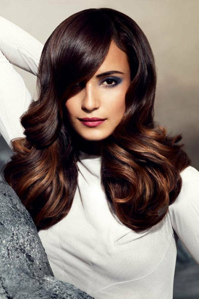 smooth and shiny hairstyle, with side-parting and curls, brunette hair colors, dark brown with dark blonde highlights, on woman in white jumper, with blue eye make up, and pink lipstick