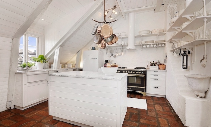 white kitchen with rough brown tiled floor, wooden kitchen island painted in white, shelves with various utensils, shabby chic decorating