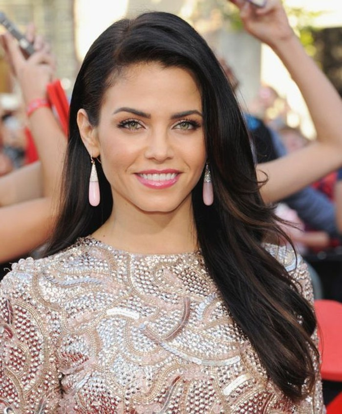 large pink drop earrings, and a sparkly silver dress, with beads and sequins, worn by smiling green-eyed woman, with long wavy, side-swept hair with discreet highlights, dark brown hair colors