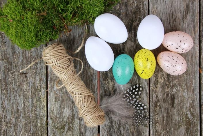 string and green moss, several fluffy grey quail feathers, with white spots, three large white eggs, two smaller speckled pastel pink eggs, a yellow and a teal egg, ideas for coloring easter eggs