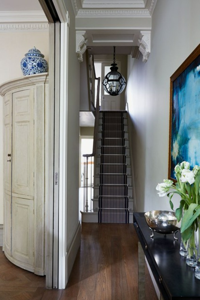 narrow stairs with striped rug, dark wooden floor, walls with plaster details, blue framed painting, near table with tulips in vases, hallway decor