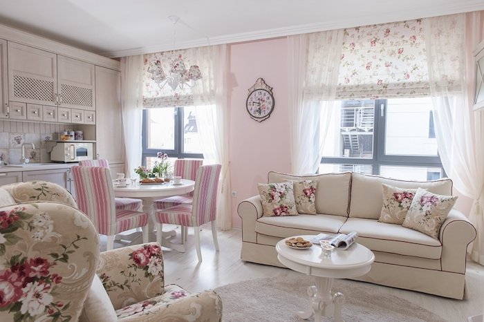 cream shabby chic sofa, with floral cushions, armchair with a matching floral pattern, near white round antique coffee table, in living room with pale pastel pink walls, shabby sheek