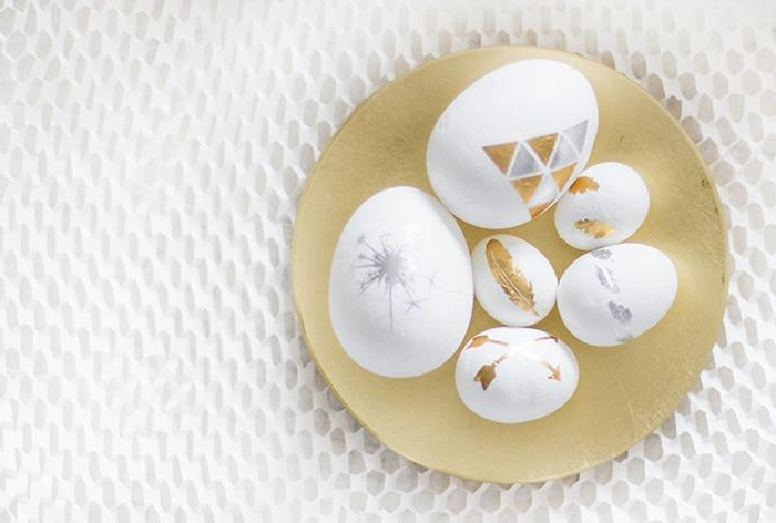 differently sized white eggs, covered with gold and silver tattoos, featuring geometric shapes, arrows and feathers, a sparkler and others, easter egg decorating, placed inside a round, flat golden dish
