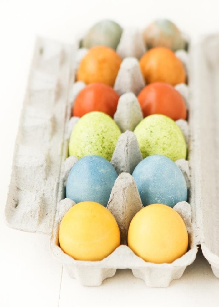 a dozen naturally colored eggs, easter egg ideas, in pale yellow, spotty blue and green, two shades of orange, and multicolored, dyed using tea