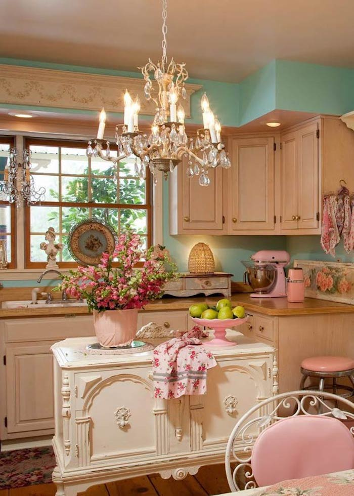 crystal chandelier hanging in shabby chic kitchen, pastel blue walls and pastel pink furniture, white ornamental kitchen island, many decorative items and a flower pot