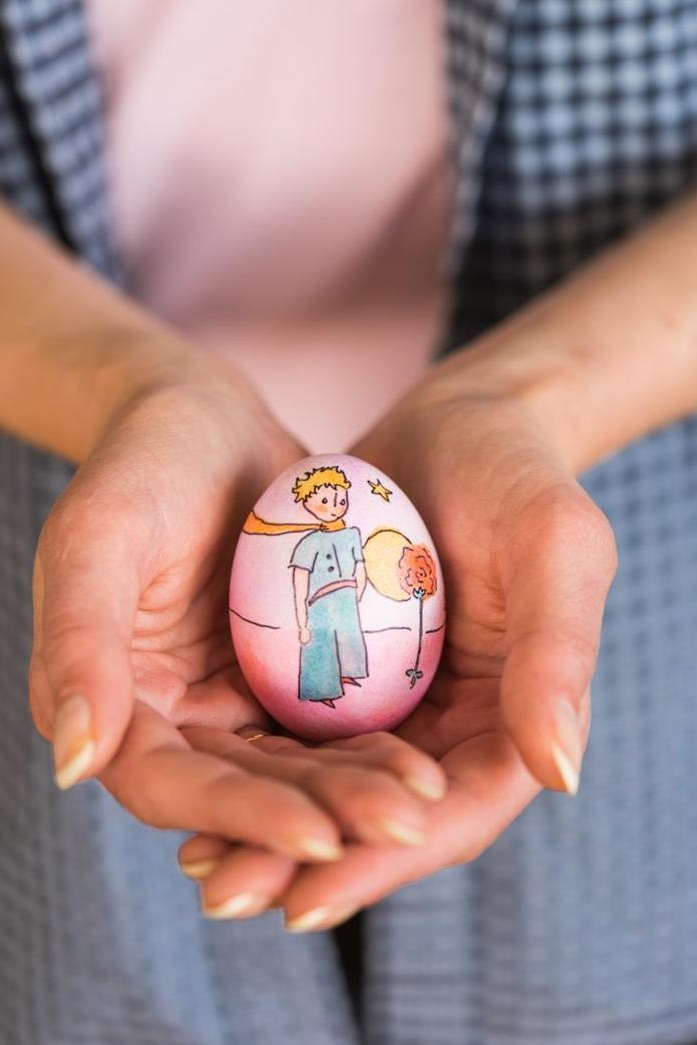 simple drawing of Antoine de Saint-Exupéry's the little prince, in full color, done on a pink easter egg, held by two hands