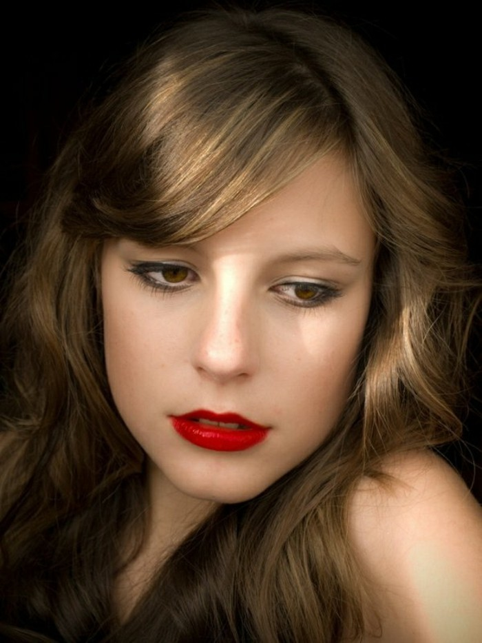 retro black eyeliner, mascara and red lipstick, on young woman, with medium length brown hair, and honey blonde highlights