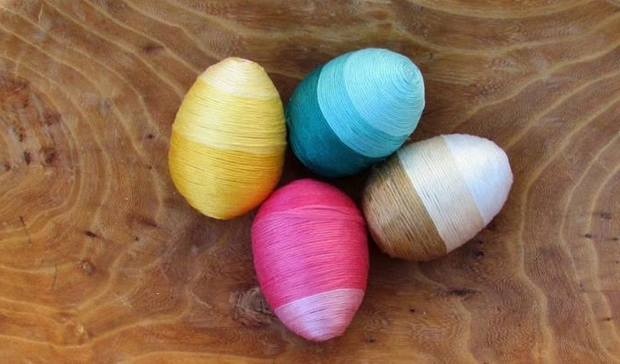 colorful thread in different shades of pink, yellow teal and brown, wrapped around four eggs, easter egg decorating, placed on wooden surface