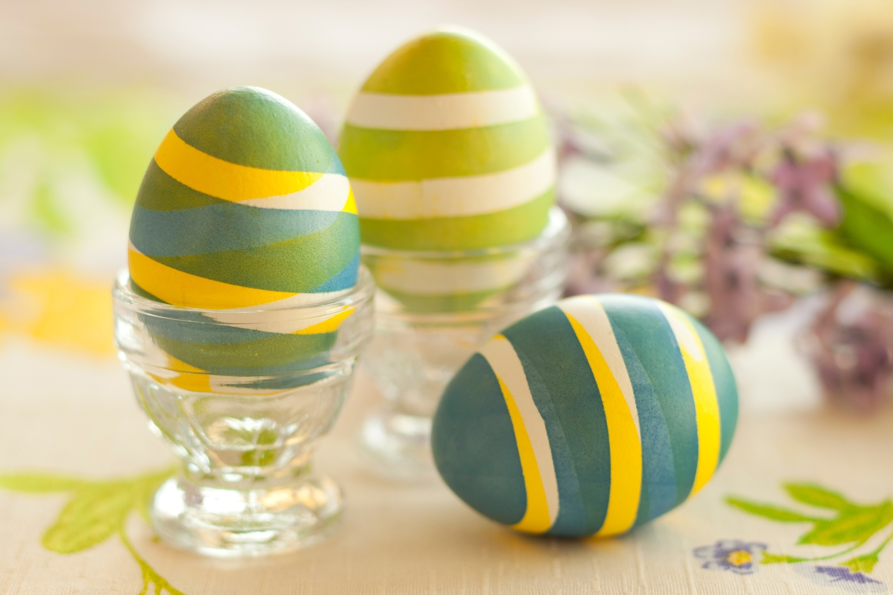striped eggs in different shades of green, with white and yellow, how to dye easter eggs, two in clear glass dishes, one placed on the table