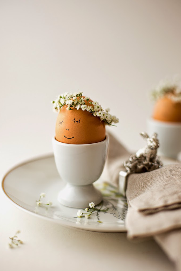 plain brown egg, with a tiny white flower crown, and minimalistic face, drawn on it in black sharpie, easter egg designs, placed in a white ceramic egg dish, on a plate
