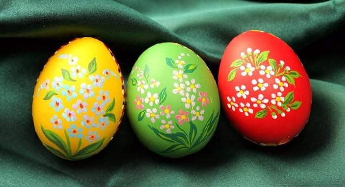simple white and orange flowers, with green leaves, painted on easter eggs, dyed in red green and yellow