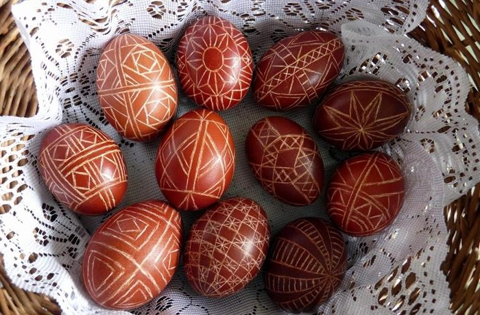 wax decorated eggs, dyed in red, and featuring complex, symmetrical geometric patterns, easter egg coloring, placed on a white doily, in a wicker basket