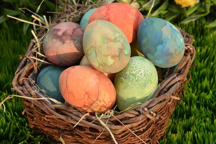 watercolor effect spotty eggs, in orange and green, blue and pink, easter egg coloring techniques, placed in a basket made of twigs