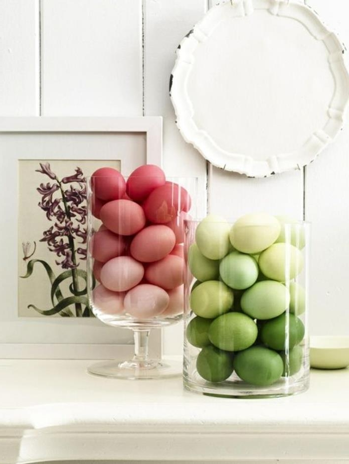 clear glass containers, filled with different shades of green, and red easter eggs respectively, placed on a white shelf, near a framed drawing of a flower, and a decorative plate