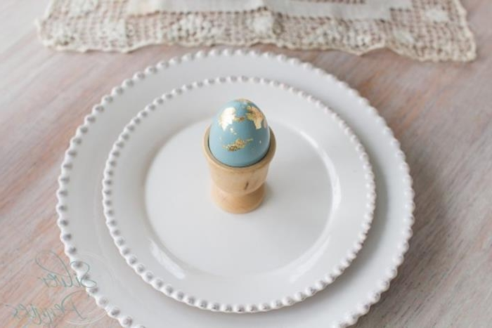 a single pale blue egg, decorated with gold leaf, placed in a beige egg dish, on top of two ornate, round white ceramic dishes