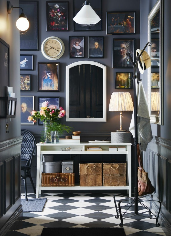 many framed images, on black wall, inside a hallway with black and white tiled floor, white cupboard containing storage boxes