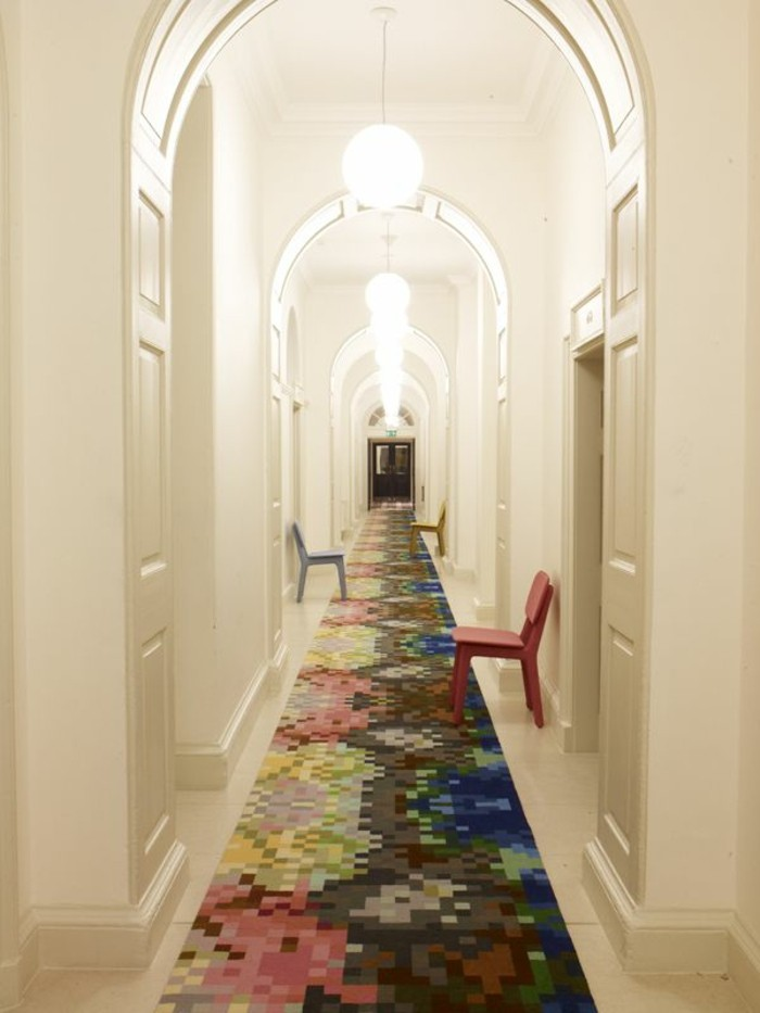 narrow and very long corridor, with white walls and several white doors, lit round ceiling lamps, three chairs in different colors, long hallway runners, multicolored rug covering the floor