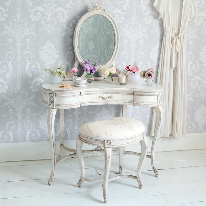 vanity in antique french style, painted in white, and featuring an oval mirror, and a matching stool, shabby chic decorating, different flowers in vases and cups
