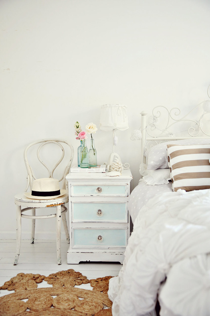 shabby chic furniture, vintage chair with white chipping paint, antique pale blue and white cupboard, bed with white wrought-iron frame, and soft white bedding